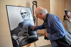 Carlos Saura realizando la tradicional firma de su retrato